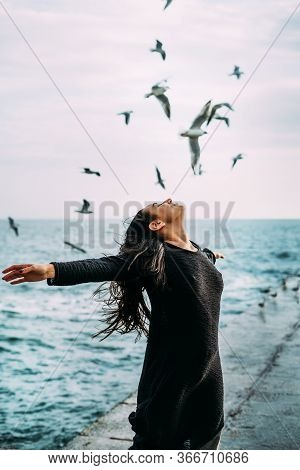 Close-up A Young Girl In Black Clothes Is Standing By The Sea With A Strong Wind. Seagulls Fly. The