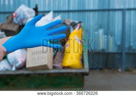 A Man Wears Rubber Gloves For Garbage Collection. A Lot Of Garbage In The Container. Garbage Collaps