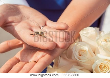 The Hands Of Newlyweds Hold The Key To The Lock Of Love, A Symbol Of A Strong Marriage. Wedding Trad