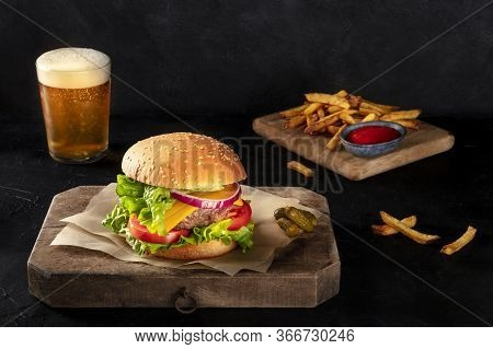 Burger With French Fries And Beer. Hamburger With Beef, Cheese, Onion, Tomato, And Green Salad, On A
