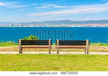 Two Benches On The Sunny Beach Shore. Beautiful Skyline View From Empty Park With Paved Footpath On