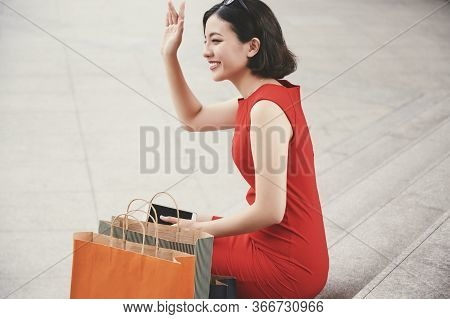Beautiful Young Asian Woman Sitting On Steps Outdoors With Many Shopping Bags And Waving With Hand T