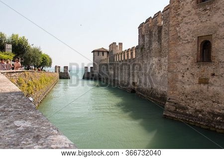 Italy, Lombardy - August 05 2018: The View Of Ancient Walls And Moat Of Scaliger Castle On August 05