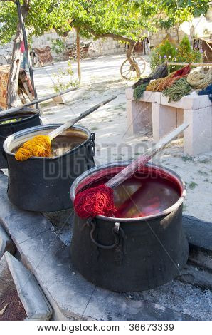 Photo Of Traditional Dye Pots For Yarn With Yarn Looped On Stick