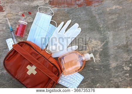 First Aid Kit On Old Wooden Background. Concept Of Protect Yourself From Covid-2019. Top View.
