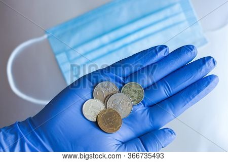 A Gloved Hand Holds Ruble Coins Against The Background Of Medical Masks. The Concept Of Scarcity And