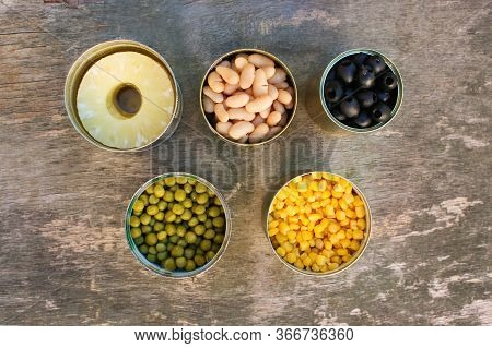 Different Open Canned Food On Old Wooden Background. Top View.