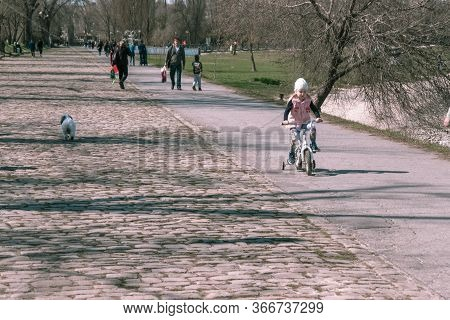 Taganrog, Russia - 07.04.19: Little Girl In A Pink Jacket Rides A Bicycle. A Child Learns To Ride A