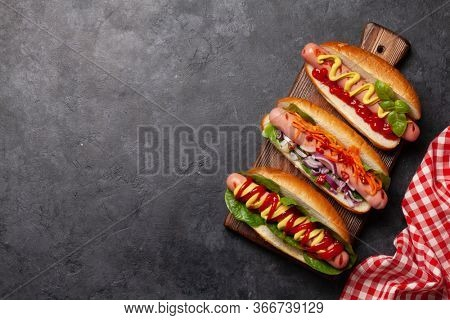 Various hot dog with vegetables, lettuce and condiments on wooden board. Top view with copy space. Flat lay