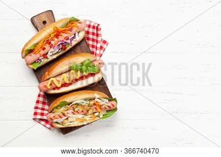 Various hot dog with vegetables, lettuce and condiments on wooden background. Top view with copy space. Flat lay