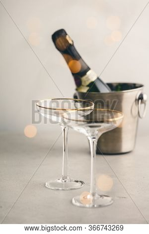 Champagne bottle in bucket with ice and glasses, vertical composition