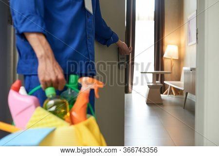 Worker With Bucket Of Detergents And Sprays Opening Door Of Apartment He Needs To Clean