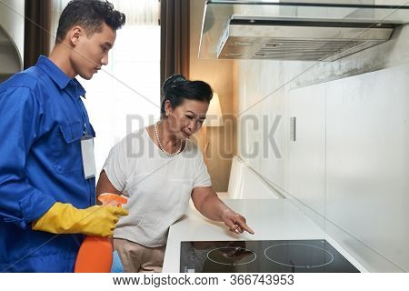 Senior Vietnamese Woman Asking Cleaning Service Worker To Wipe Induction Stove With Detergent To Rem