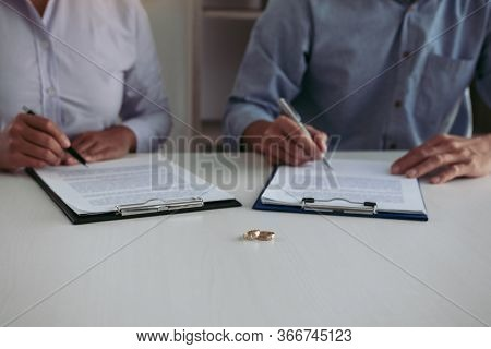 Husband And Wife Crate Signing Divorce Documents At Lawyer Office.