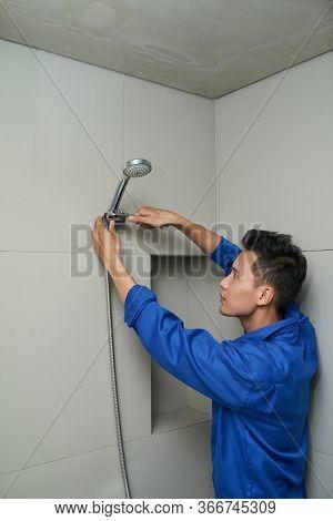 Serious Vietnamese Plumber In Uniform Fixing Leaking Shower Head In Bathroom