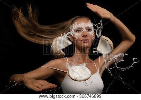 Woman with applied fresh coconut mask on the face smashes coconut with her palm, splashing out coconut water on black background . Karate Chop