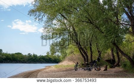 Russia. Krasnodar On April 30, 2020. Cyclists Relax In The Parking Lot. The Bank Of The Kuban River.