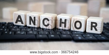 Anchor - Text Cubes Stand On A Black Keyboard On A Wooden Table