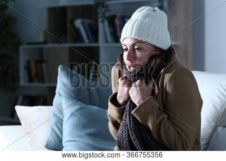 Cold Adult Woman Covered With Clothes Freezing Sitting On The Sofa At Night At Home