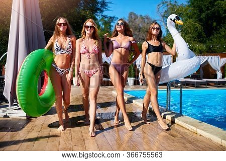 Hot Pretty Girls In Bikini Walking Together With Inflatable Swan, Swim Ring By Swimming Pool. Attrac