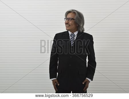 Happy Asian Senior Businessman In Black Suit And Eyeglasses Standing Over White Wall Background, Bus