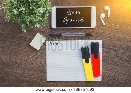 Learn Spanish Inscription, Smartphone, Wireless Headphones, Notepad With The Word Hello In Spanish,