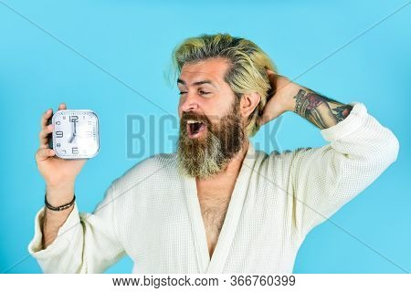 Happy Man Being Awakened By Alarm Clock In Bedroom. Mature Man Turning Off Clock. Mature Man Turn Of