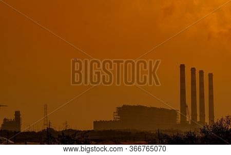 Power Plant With Orange Sunset Sky And Birds Flying On The Sky. Air Pollution Concept. Energy For Su