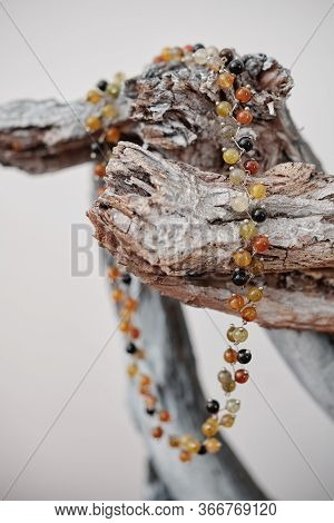 Beautiful Necklace Made Of Amber Beads On Wooden Snag, Selective Focus