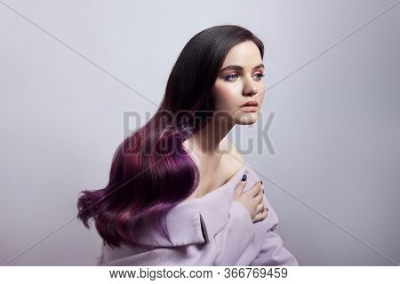 Portrait Of A Woman With Bright Colored Flying Hair, All Shades Of Purple. Shiny Healthy Colored Hai