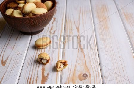 Homemade Russian Nuts With Condensed Milk On A Light Background, Wafer Napkin. Cut Nuts With Condens