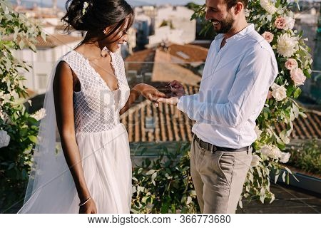 Mixed-race Wedding Couple - African-american Bride And Caucasian Groom. Groom Puts A Ring On Brides