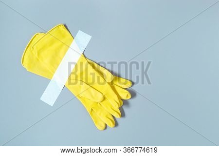Yellow Gloves Glued With Tape On Wall. Pair Of Protective Gloves For Cleaning Work Isolated On Backg
