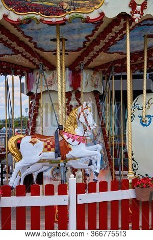 Old Carousel In A Holiday Park. Horses And Airplane On A Traditional Fairground Vintage Carousel. Me