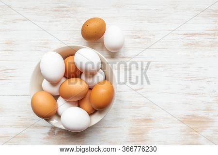 Brown And White Eggs In Bowl On Wood Background. Plate With Brown And White Chicken Eggs On Wooden T