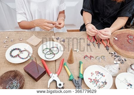 Women Using Various Tools When Making Beautiful Jewelry Like Earrings And Bracelets With Natural Sto
