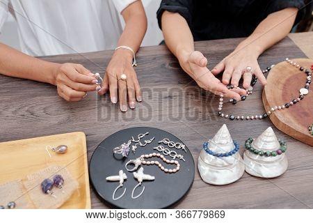 Women Choosing Beautiful Handmade Jewelry From Counter In Shop