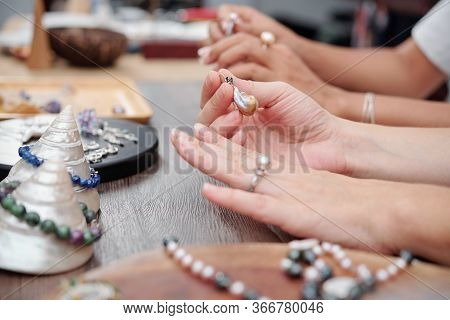 Close-up Image Of Woman Trying On Rings And Earrings With Natural Stones When Shopping At Jewelry St