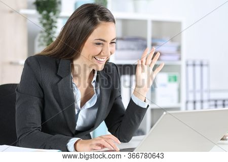 Happy Executive Woman Greeting On Videocall On Laptop Sitting On Her Desk At Office