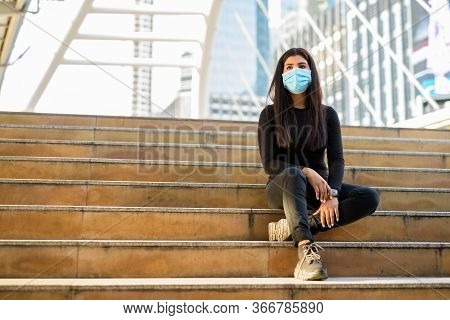 Full Body Shot Of Young Indian Woman With Mask Sitting On Stairs At The Skywalk Bridge