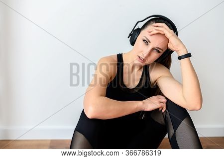 Sport Lifestyle, Sport Fashion. Attractive Young Girl In A Black Sports Outfit And In Headphones Loo