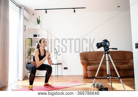 Recording Fitness Video Tutorial At Home. Attractive Slender Girl Does Exercises And Records Herself