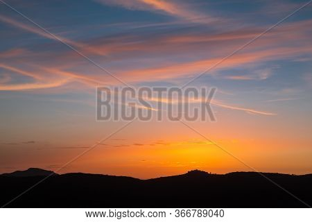 Orange And Purple Afterglow Of Sunset Behind The Silhouetted Ancient Mountain Village Of Sant'antoni
