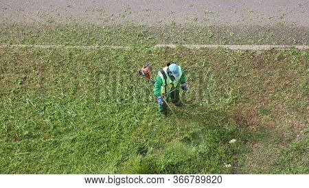 Kryvyi Rih, Kryvyi Rih / Ukraine-may 17, 2020: A Man In Special Clothes Mows The Lawn. A Worker In A
