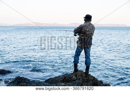 Fisherman fishes for spinning on rocks by the sea