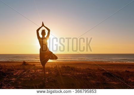 Young Woman Doing Yoga Exercise Tree-pose.silhouette Meditation Girl On The Background Of The Stunni