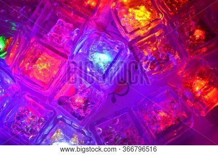 Many Different Colors Of Small Plastic Luminous Ice Cubes Floating In Water Are Located In Ukrainian