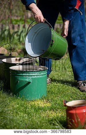 Several Old Buckets Are Standing On The Grass In Sunny Weather. Grandmother Pours The Collected Wate