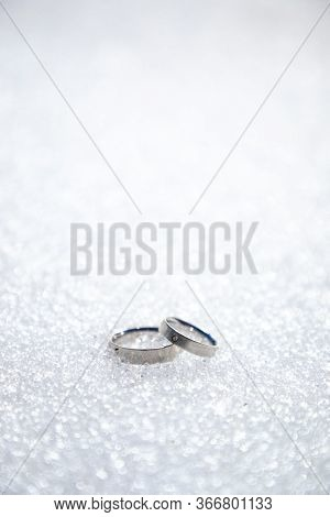 Silver Or White Gold Engagement Rings On Snow Or Sparkling White Background