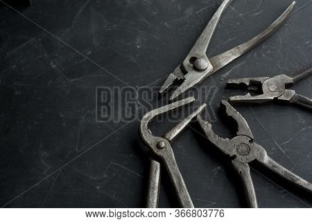 Old Vintage Pliers On A Dark Concrete Background, Close Up, Copy Space